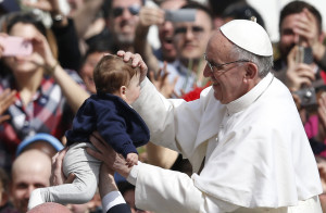 Pope Francis blesses a child in St. Peter's Square after celebrating Palm Sunday Mass at the Vatican March 24. (CNS photo/Paul Haring) (March 25, 2013) See POPE-PALM March 25, 2013.